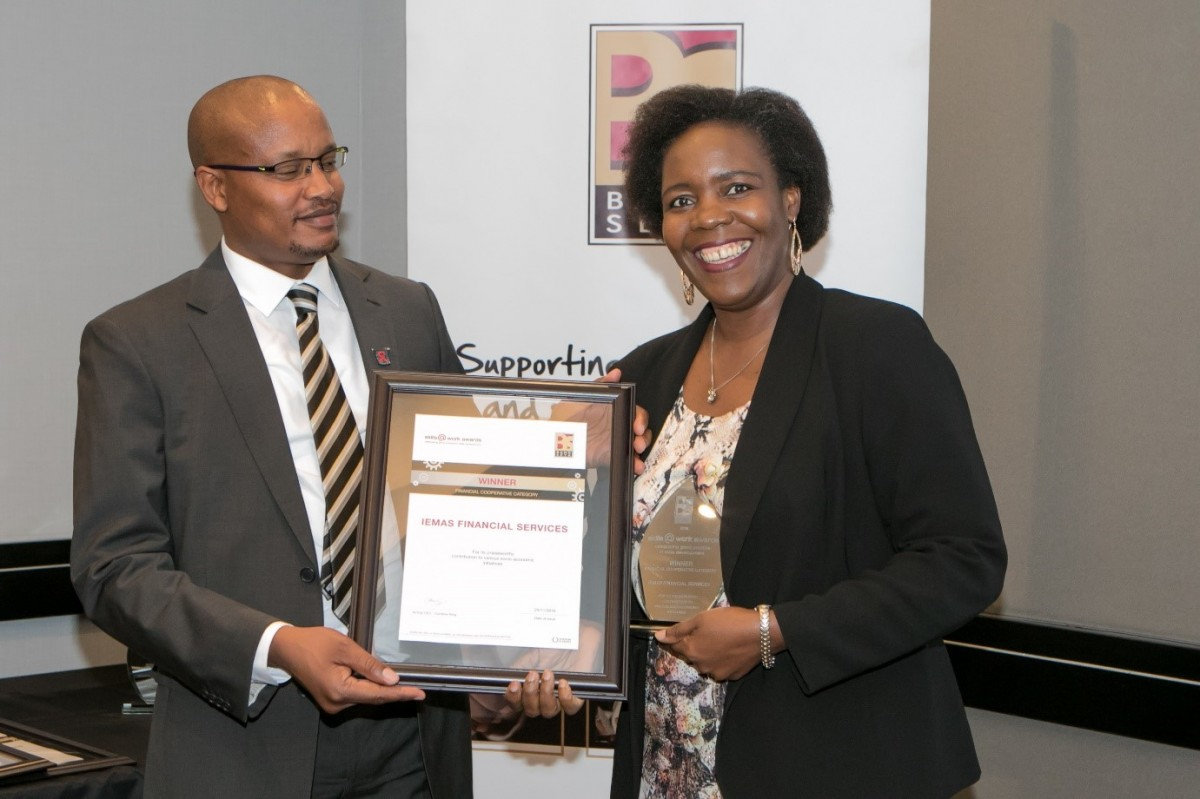 An African HR representative handing over a certificate and trophy to an African lady in a corporate setting.