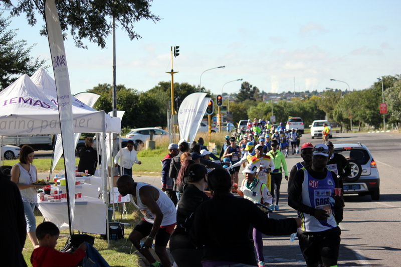 Iemas employees assist runners at a marathon with rehydration