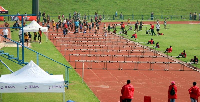 Children competing in an athletics championship in the hurdles heat.
